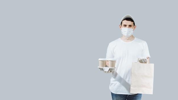 Een jonge voedselleverancier in een beschermend masker en handschoenen houdt dozen met voedsel vast en geeft de klant een snelle levering van eten en drinken.
