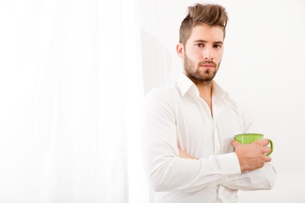 Een jonge volwassen man die thuis koffie drinkt.