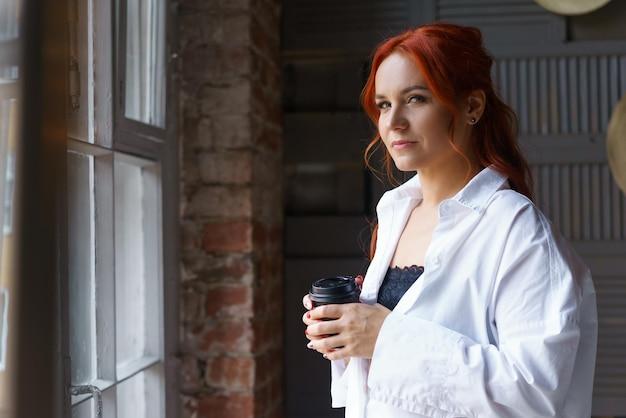 Een jonge volwassen roodharige vrouw in een wit overhemd staat bij het raam en houdt een glas koffie vast