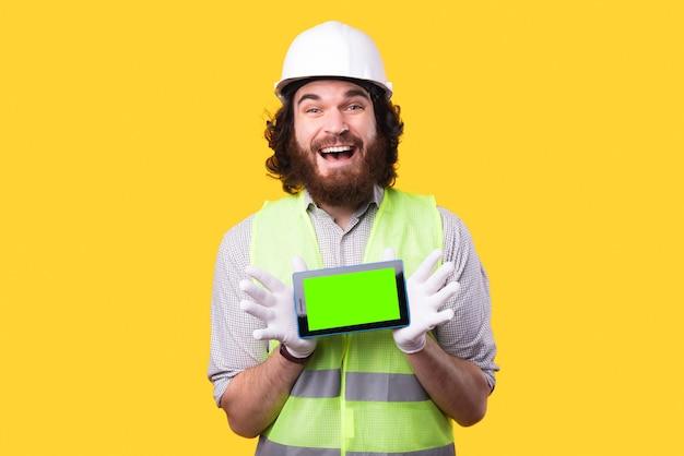 Een jonge vrolijke ingenieur houdt een gloednieuwe tablet vast en kijkt naar de camera bij een gele muur