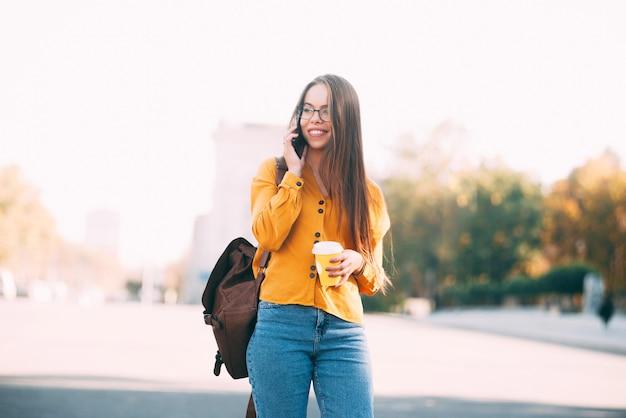 Een jonge vrolijke jonge vrouw loopt en praat met haar telefoon wegkijken en houdt een kop warme drank vast