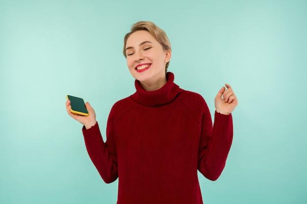 Een jonge vrolijke vrouw in een rode trui met een smartphone op een blauwe achtergrond