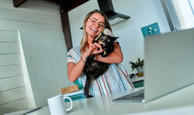 Een jonge vrolijke vrouw in vrijetijdskleding en een bril speelt met een kat en praat aan de telefoon terwijl ze thuis in haar keuken op een laptop werkt.