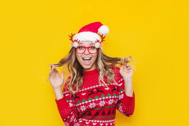 Een jonge vrolijke vrouw met een kersttruihoed en een bril houdt haarlokken in haar handen