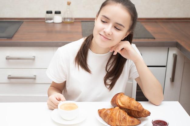 Een jonge vrouw aan een tafel in de keuken aan het ontbijt, glimlachen, praten, verse croissants eten. is koffie aan het drinken
