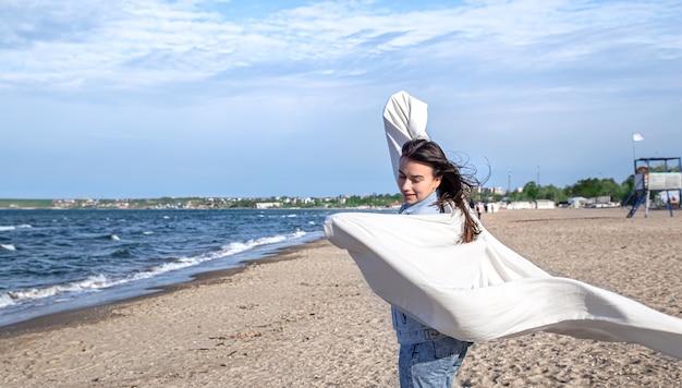 Een jonge vrouw aan zee heeft plezier met het vasthouden van een groot laken in de wind, een vrije levensstijl.