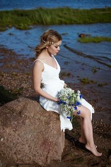Een jonge vrouw alleen in een witte jurk zit op een steen aan de kust met een boeket in haar hand in de zomer bij zonnig weer