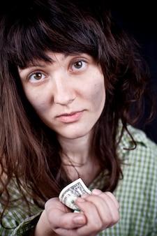 Een jonge vrouw bedelen met wat geld in haar handen.
