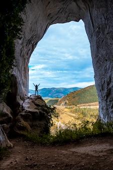 Een jonge vrouw beklimt de helling van de grotten van ojo de aitzulo in oñati met één arm omhoog