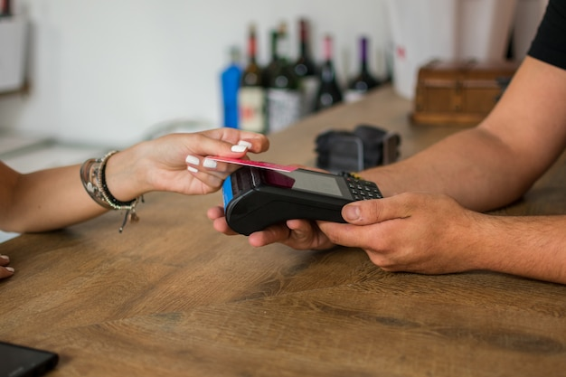 Een jonge vrouw betaalt met creditcard in een pub.