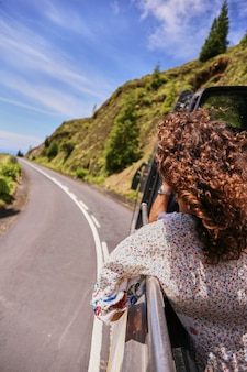 Een jonge vrouw bewondert een prachtig uitzicht op de bergen vanuit het raam van een