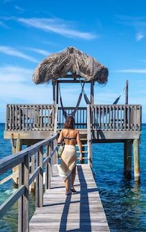 Een jonge vrouw bij een houten constructie van de caribische zee op roatan island. honduras