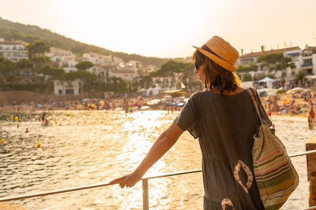 Een jonge vrouw bij zonsondergang aan de kust van tamariu in de stad palafrugell. girona, costa brava in de middellandse zee