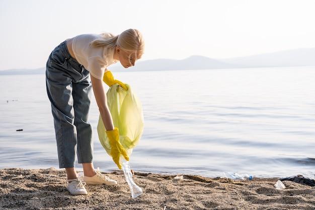 Een jonge vrouw bukt zich en pakt een lege plastic fles op om die in de vuilniszak te doen. behoud van de natuur en respect voor de planeet.