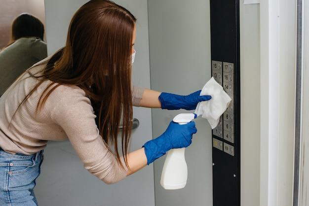 Een jonge vrouw desinfecteert en reinigt sleutels in een lift tijdens een wereldwijde pandemie. blijf thuis