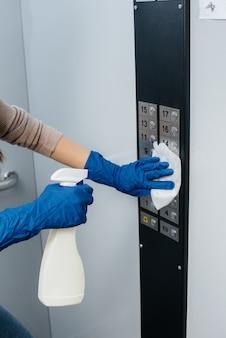 Een jonge vrouw desinfecteert en reinigt sleutels in een lift tijdens een wereldwijde pandemie. blijf thuis.