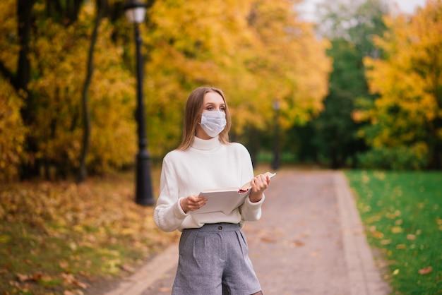 Een jonge vrouw die beschermt tegen het coronavirus tijdens het wandelen in het park. herfst achtergrond.