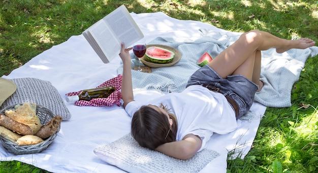 Een jonge vrouw die bij een picknick een boek leest