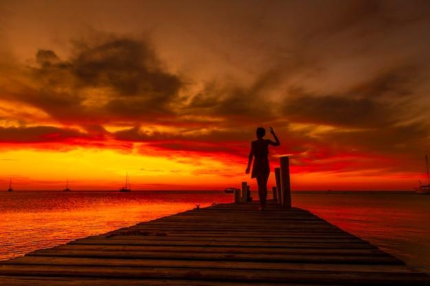 Een jonge vrouw die bij zonsondergang op het strand van west end in roatan naar de caraïbische zee loopt