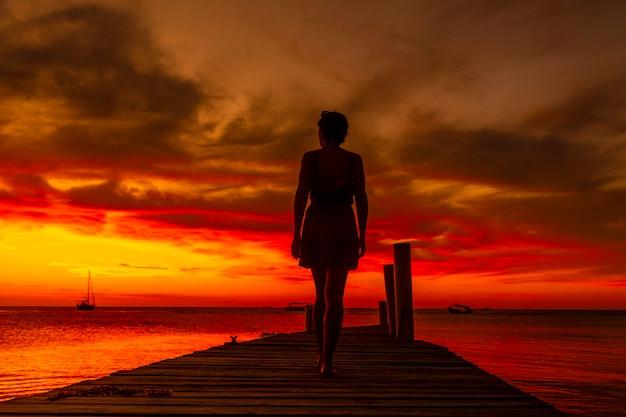 Een jonge vrouw die bij zonsondergang op het strand van west end in roatan naar de zee loopt