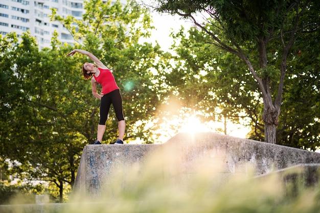 Een jonge vrouw die buiten in de stad aan het sporten is, zich uitstrekt.
