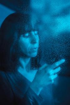 Een jonge vrouw die de mobiele telefoon op een regenachtige nacht bekijkt