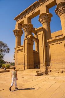 Een jonge vrouw die de tempel van philae binnengaat met zijn prachtige zuilen, een grieks-romeinse constructie, een tempel gewijd aan isis, de godin van de liefde. aswan. egyptische