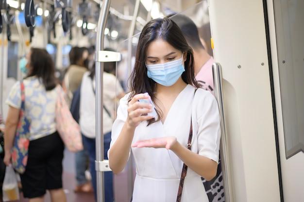 Een jonge vrouw die een beschermend masker in de metro draagt, gebruikt alcohol om handen te wassen, te reizen onder covid-19 pandemie, veiligheidsreizen, sociaal afstandsprotocol