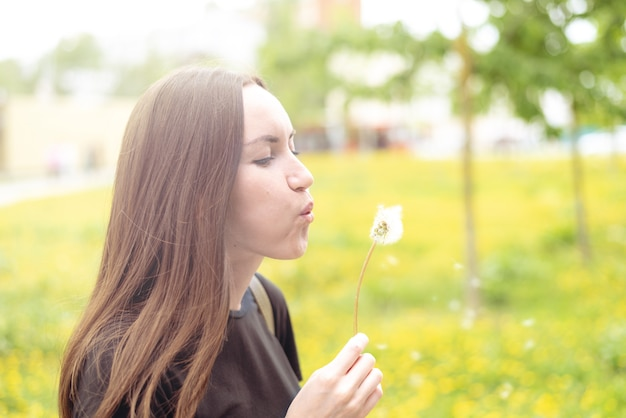 Een jonge vrouw die een bloeiende paardebloem in haar hand houdt en op een bloem blaast