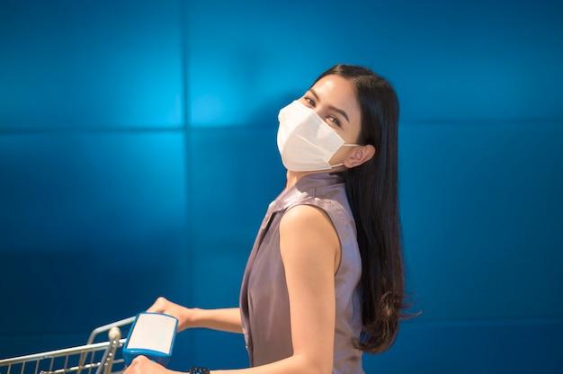 Een jonge vrouw die een chirurgisch masker met een karretje draagt in winkelcentrum, covid-19 en pandemisch concept