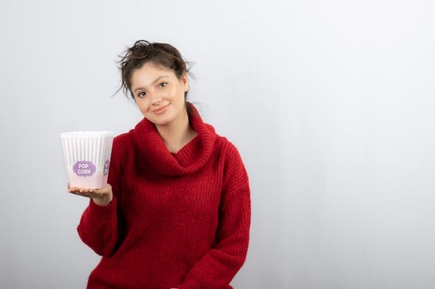 Een jonge vrouw die een emmer popcorn vasthoudt.