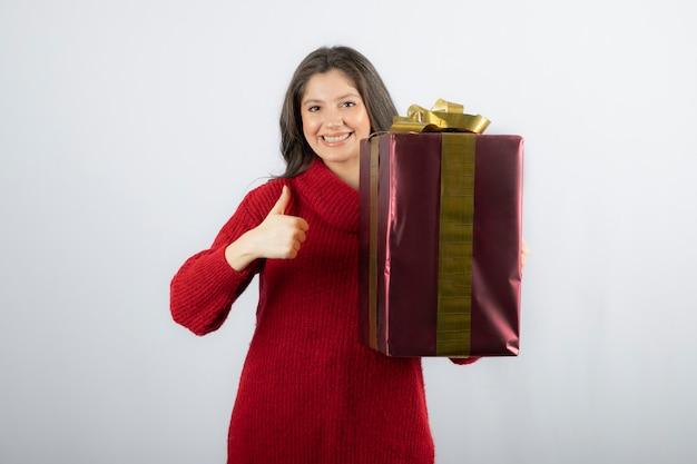Een jonge vrouw die een geschenkdoos vasthoudt en een duim toont.