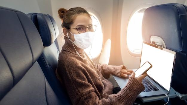 Een jonge vrouw die een gezichtsmasker draagt, reist met het vliegtuig, nieuwe normale reizen na covid-19 pandemisch concept