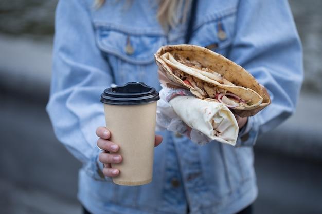 Een jonge vrouw die een glas koffie en snel voedsel houdt.