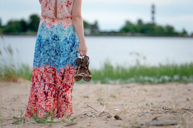 Een jonge vrouw die een kleurrijke lange kleding en schoenen in haar handen draagt die zich op het strand bevinden en de vuurtoren bekijken. uitzicht vanaf de achterkant