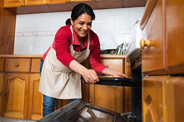 Een jonge vrouw die een metalen dienblad met versierd rauw deeg in de oven zet, in een keuken, ze draagt een schort