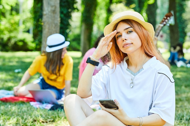 Een jonge vrouw die een telefoon vasthoudt en op het gras zit met haar vrienden op de rug.