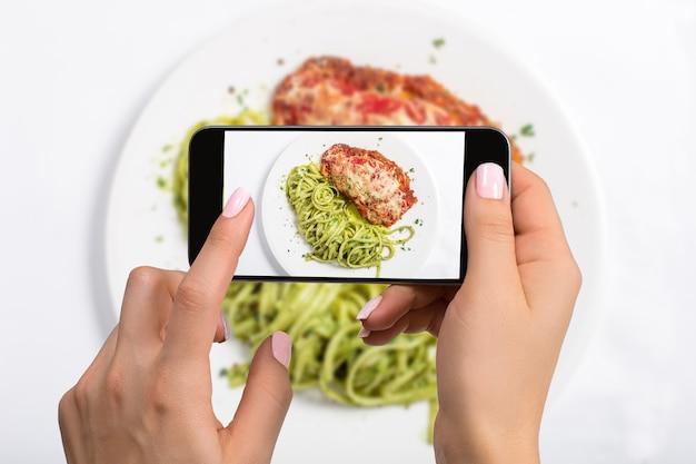 Een jonge vrouw die foto's maakt van voedsel op een smartphone, die een maaltijd fotografeert met een mobiele camera. gemaakt voor sociale netwerken. bovenaanzicht mobiele telefoon