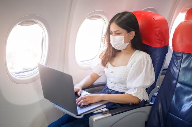 Een jonge vrouw die gezichtsmasker draagt, gebruikt laptop aan boord, nieuwe normale reis na covid-19 pandemisch concept
