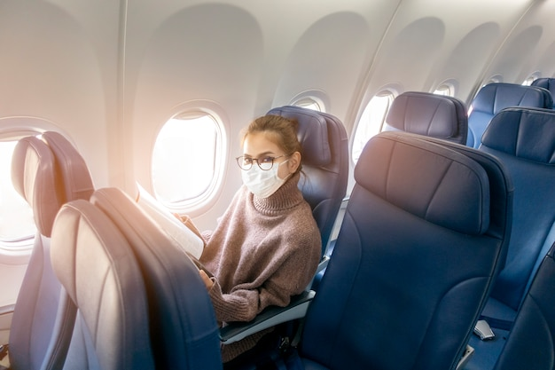 Een jonge vrouw die gezichtsmasker draagt reist op vliegtuig, nieuwe normale reis na covid-19 pandemisch concept