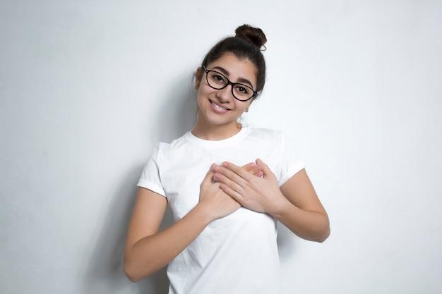 Een jonge vrouw die haar hartelijke dankzegging toont door haar handen dichtbij het hart te houden