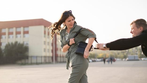 Een jonge vrouw die in de stadsstraat loopt en inbreker probeert haar zak, het misdadige en geweldconcept te stelen