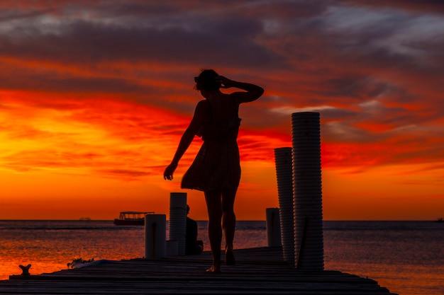 Een jonge vrouw die in de zonsondergang op het strand van west end in roatan loopt
