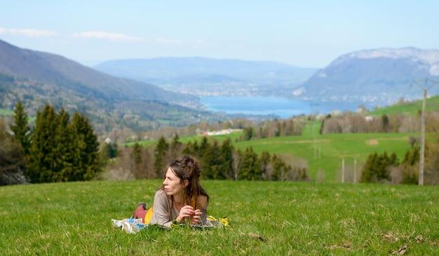Een jonge vrouw die in het gras ligt
