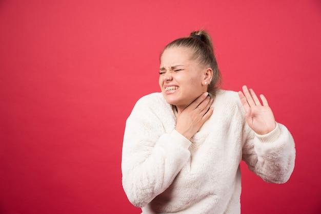 Een jonge vrouw die keel vasthoudt en aan pijn lijdt