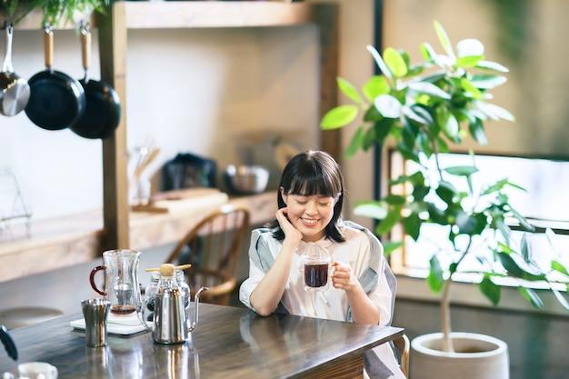 Een jonge vrouw die koffie zet en drinkt in een rustige sfeer