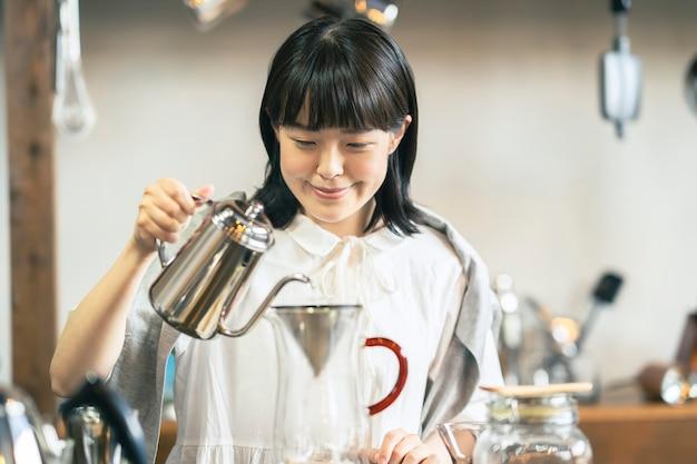 Een jonge vrouw die koffie zet in een ontspannende ruimte