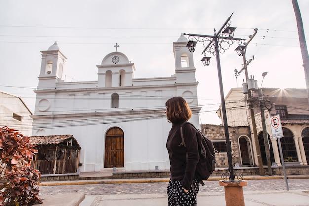Een jonge vrouw die naar de witte kerk in de stad copan ruinas in honduras kijkt