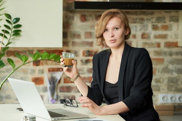 Een jonge vrouw die op afstand in haar keuken werkt. een vrouwelijke baas die koffie drinkt voor een videoconferentie met haar werknemers thuis.