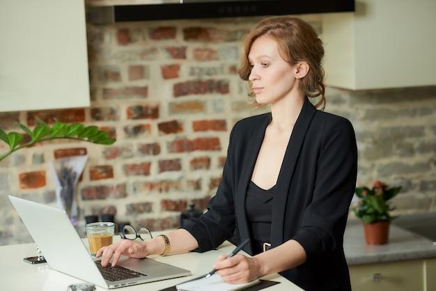 Een jonge vrouw die op afstand in haar keuken werkt. een vrouwelijke baas op zoek naar nieuws tijdens een videoconferentie met haar werknemers thuis.